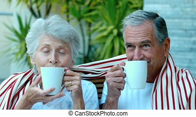 Retired couple enjoying coffee outs