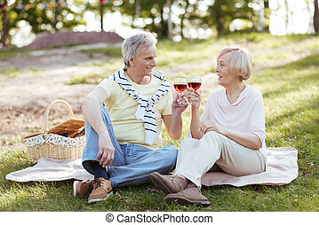 Retired couple enjoying picnic and weather in the park
