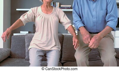 Retired couple flopping down on the couch in slow motion