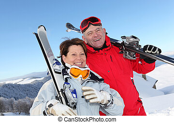 Retired couple having fun on a skiing trip