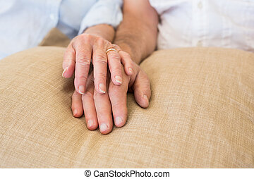 Retired couple holding hands at home in living room