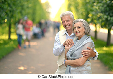 Happy smiling retired couple posing in park