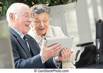 Retired couple laughing at image on tablet screen