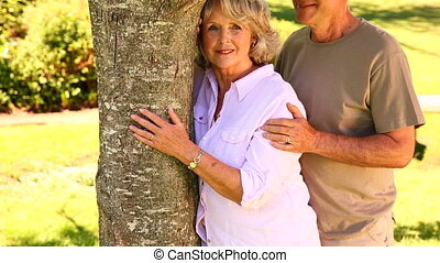 Retired couple leaning against tree smiling at camera at...
