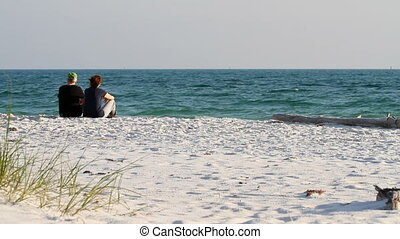 Retired Couple Sitting At Beach - Retired couple sit at the...