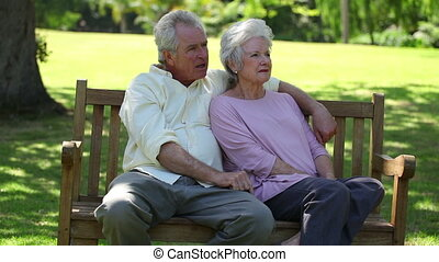 Retired couple sitting on a bench