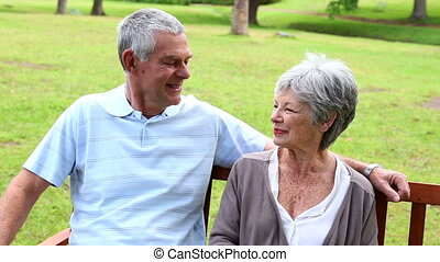 Retired couple sitting on a park bench