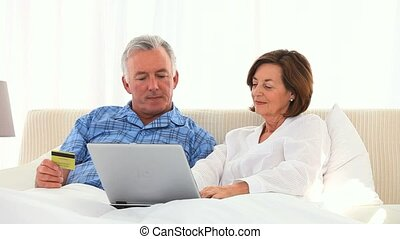 Retired couple using a credit card on internet