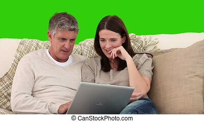 Retired couple using a laptop on their living room