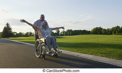 Retired couple, wife on wheelchair enjoying life