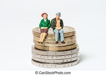 Retired / elderly couple sitting on euro coins
