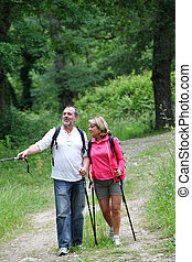 Retired elderly people hiking in forest pathway