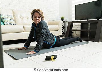 Retired Female Learning Exercise Online At Home - Senior ...