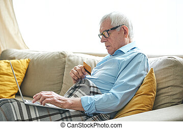 Retired grey-haired man wrapped in plaid relaxing on couch and shopping online