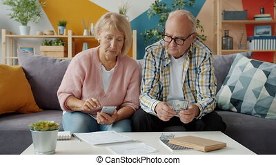 Retired man and woman counting money reading financial ...