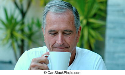 Retired man enjoying coffee outside