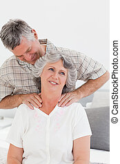 Retired man giving a massage to his wife