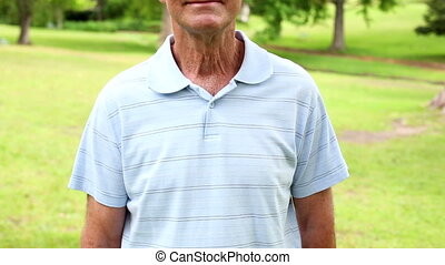 Retired man in the park smiling at