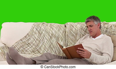 Retired man looking at a book on his sofa