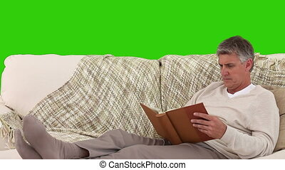 Retired man looking at an album on his sofa