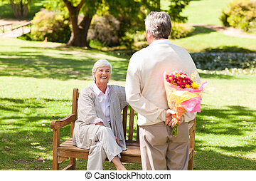 Retired man offering flowers to his