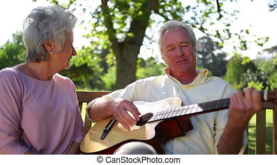 Retired man playing guitar to his wife