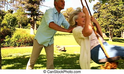 Retired man pushing his wife on swing