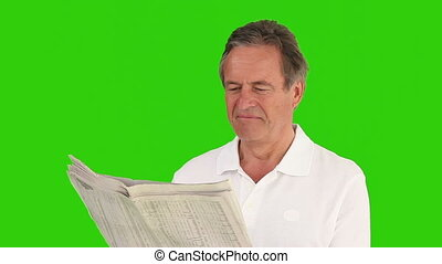 Retired man reading a newspaper and it's making him happy