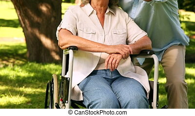 Retired man showing his disabled wife something on a sunny...