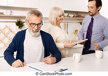 Retired man signing agreement while his wife greeting the...