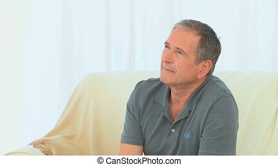 Retired man sitting and looking at the camera