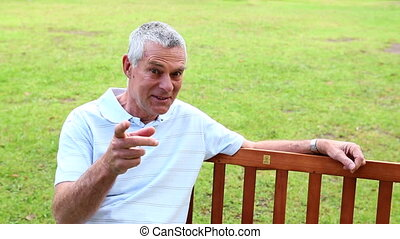 Retired man sitting on a park bench