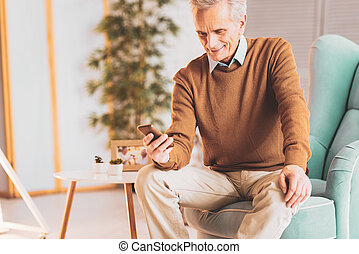 Retired man smiling while watching family photos
