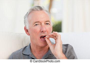 Retired man taking pills