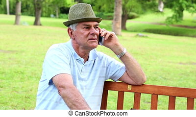 Retired man talking on the phone on a park bench