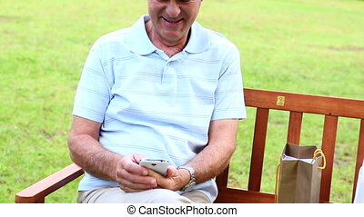 Retired man texting on the phone