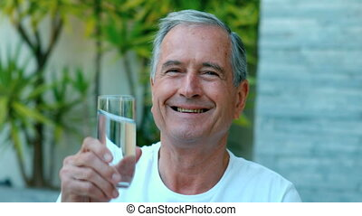 Retired man toasting with water out