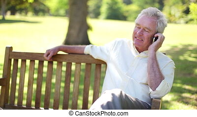 Retired man using a mobile phone on a bench