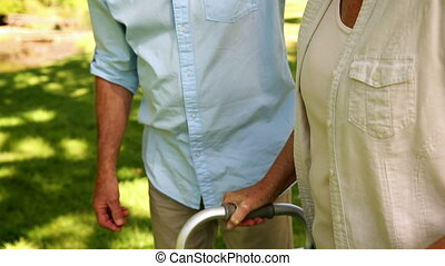 Retired man walking with his wife using a walker on a sunny...