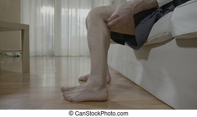 Retired man with muscular cramp sitting in bedroom rubbing...