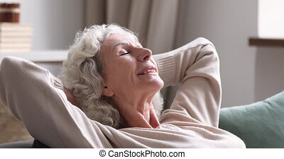 Retired mature hoary woman daydreaming on comfortable sofa.