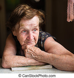Retired russian woman sitting at a table in the house.