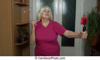 Retired senior woman doing workout, training, fitness, sport activity exercises during coronavirus
