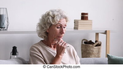 Retired woman feeling eyes tension due to computer overwork.