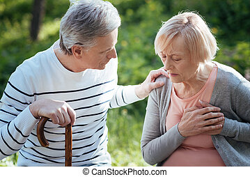 Retired woman feeling pain in the chest outdoors