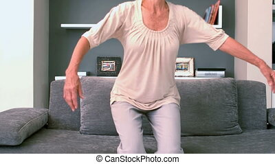 Retired woman flopping down on the couch in slow motion