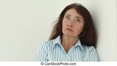 Retired woman frowning on white background - Sad retired...