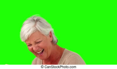 Retired woman having a laugh while she is reading a book