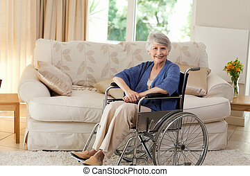 Retired woman in her wheelchair at home