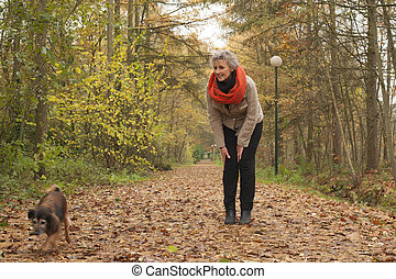 Retired woman is asking her dog to come - Middle aged woman...